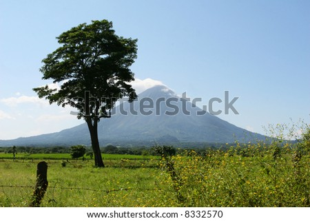 A volcano in Nicaragua looms over a beautiful pasture - stock photo