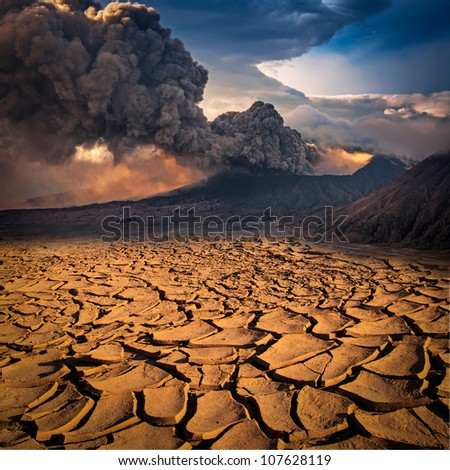 A volcano looks over a cracked earth landscape - stock photo