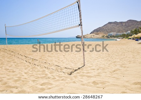 A volleyball net on an empty beach at a holiday resort. - stock photo