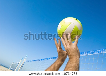 A volleyball player lobs a ball during a game at the beach. - stock photo