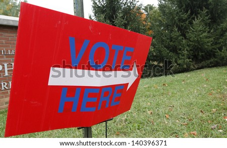 A vote here sign outside a voting station. - stock photo