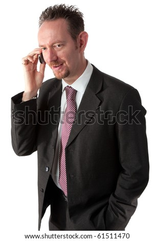 A waist up shot of a mid thirties business man talking on the phone.  The man is wearing a dark grey suit and tie.  The man is not looking at the camera but is looking in a good mood.