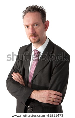 A waist up shot of a mid thirties business man.  The man is wearing a dark grey suit and tie.  The man is looking at camera and has spiky brown hair and a goatee beard.   He has his arms crossed. - stock photo