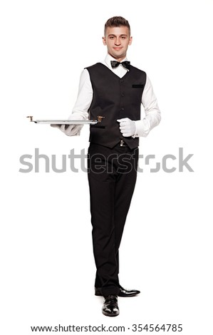 A waiter or bartender, or servant holding a silver tray and smiling. White background. - stock photo