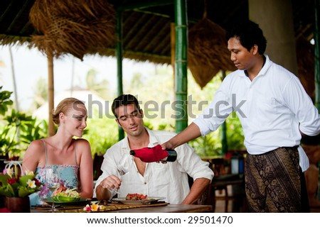 A waiter pours wine for a couple having dinner at a resort restaurant on vacation - stock photo