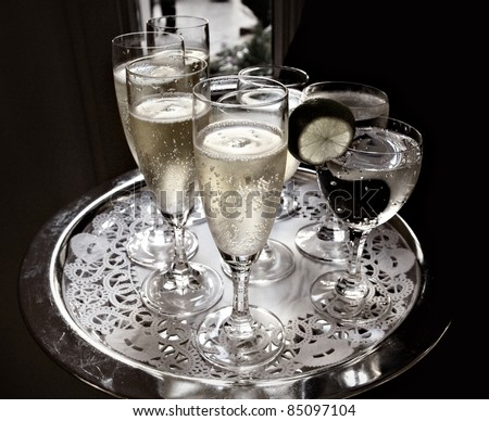 A waiter serves sparkling wine and water on a silver tray