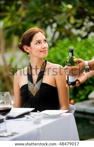 A waiter showing an attractive well-dressed woman the wine of her selection, at a formal meal outdoors - stock photo