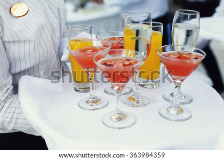 A waiter with a tray of glasses of champagne, delicious apple punch and glasses of orange juice at the reception. Glasses with alcohol - stock photo