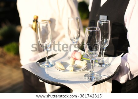 A waiter with empty wine glasses