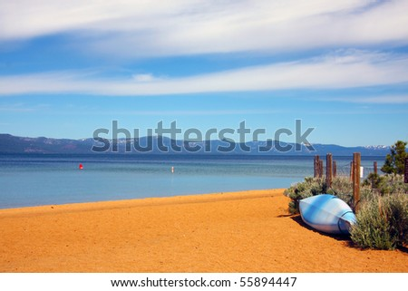 a waiting kayak on a deserted Tahoe beach on a beautiful sunny day. - stock photo