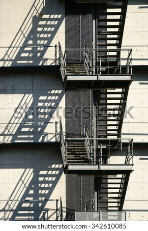 A walk outside stairway at a school building casts a shadow / External staircase casts shadows                - stock photo