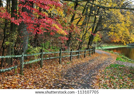 A Walking Path And Fence Along A Lake On A Rainy Day Amid The Brilliant Colors Of Autumn, Sharon Woods, Southwestern Ohio, USA - stock photo