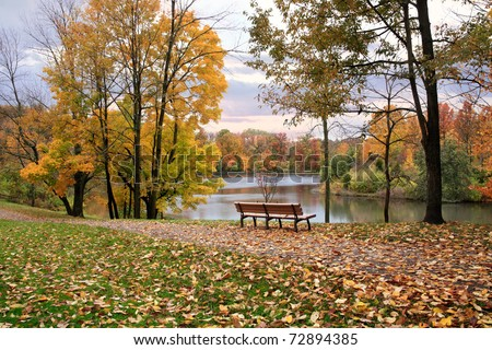 A Walking Path And Park Bench Overlooking A Lake On A Rainy Day In Autumn, Sharon Woods, Southwestern Ohio - stock photo