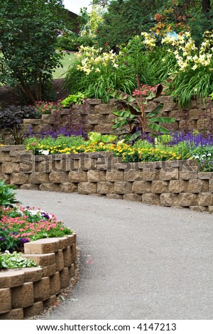 A walking path flanked by landscaping stones and lush vegetation and flowers. - stock photo