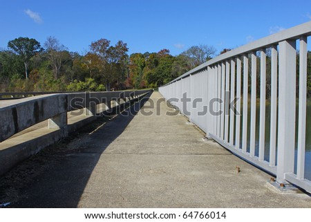 A walkway leading across a tributary along a bridge during a beautiful fall day with room for your text