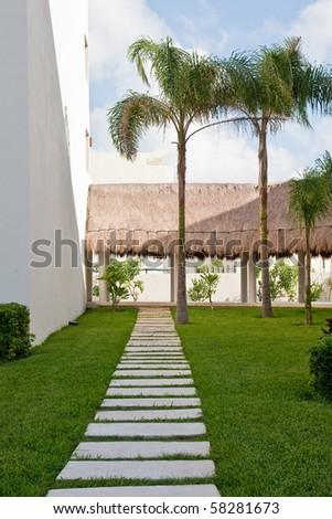 A walkway through a green grass lawn in the tropics - stock photo