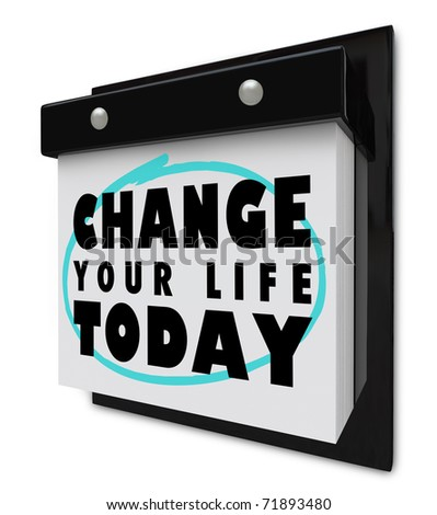 A wall calendar with tear-away pages, and words that read Change Your Life Today - stock photo