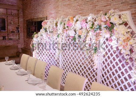 A wall decorated with white and pink flowers stand behind a restaurant table
