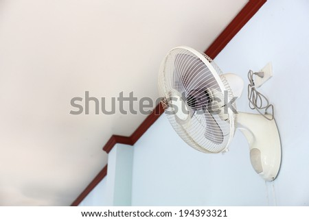 A wall fan with a pull cord switch. - stock photo