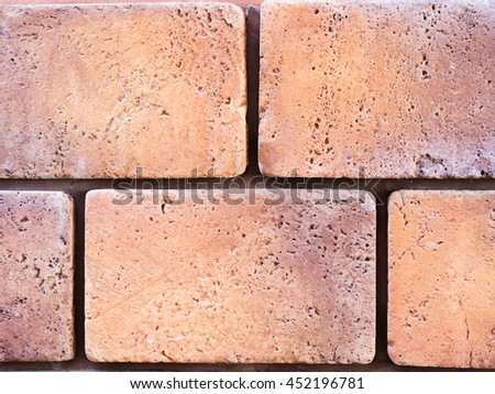 a wall from an artificial beige and red stone facade with rough fractured surfaces, laid as a brick - stock photo