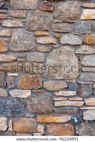 A wall of rough untreated wild stone. background texture... - stock photo