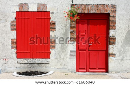 A wall with a red window and door