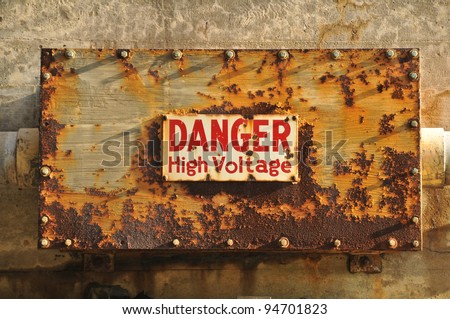 A wall with a rusty box with a Danger high voltage sign on it - stock photo