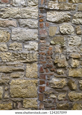 A wall with seams and bricks and stones - stock photo