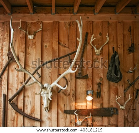 a wall with various animal horns attached in some sort of ornamental decoration in a rural area