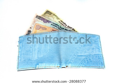 A wallet made of blue colored denim loaded with Indian currency notes. - stock photo
