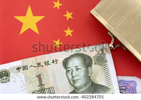 A wallet with chinese money on a Chinese flag - stock photo