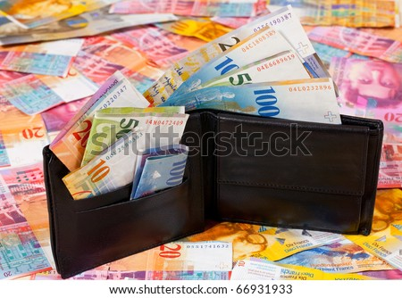 A Wallet with Swiss Francs in it, standing on a Floor with other Swiss Francs Banknotes - stock photo