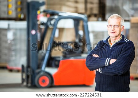 A warehouse employee is posing in front of his forklift, he is a proffesional forkliftdriver. - stock photo