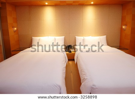 A warm and cosy bedroom in a hotel - stock photo
