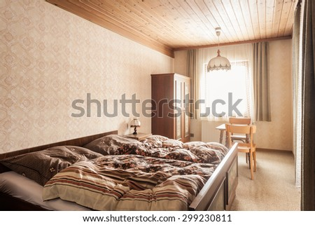 a warm bedroom in the morning with the sunlight shining through the window - stock photo
