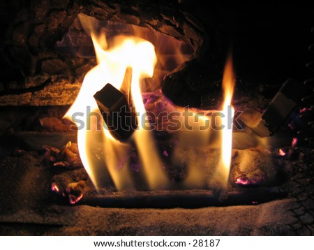 A warm fire in a home fireplace (natural gas fireplace).
