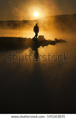 A warm, foggy sunrise silhouettes a hiker against a cold early morning mist across a lake. The mist hung perfectly still in completely calm air almost as a spirit greeting the new day. - stock photo