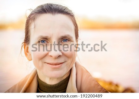 A warm portrait of a nice senior woman close to the river - stock photo