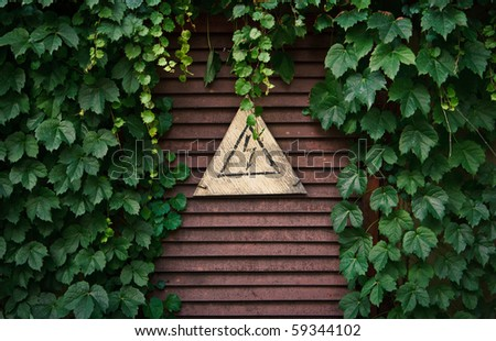 """A warning sign """"Caution High Voltage"""" hanging on a rusty ventilation grid in the frame of green plants - stock photo"""