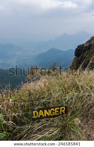 a warning sign in front of a steep cliff at the border between thailand and laos - stock photo
