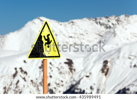 A warning sign of a possible fall from the mountain - stock photo