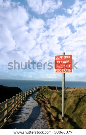 a warning sign of danger at a slippery cliff edge walk - stock photo