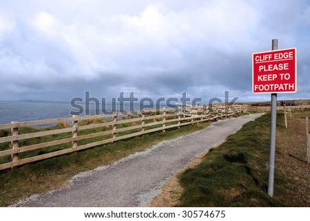 a warning sign of danger at the cliff edge walk - stock photo