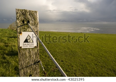 A warning sign on a cliff edge - stock photo