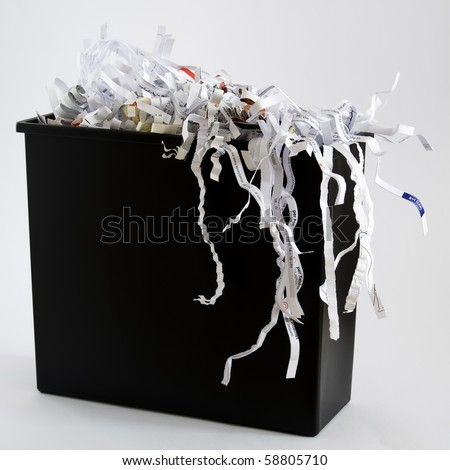 A wastebasket filled with shredded paper. - stock photo