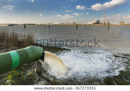 A wastewater pipe and a large oil refinery in the harbor of Antwerp, Belgium with blue sky and warm evening light. - stock photo