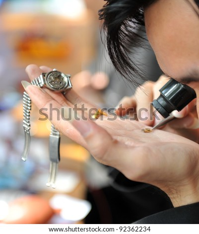 A watchmaker or repair man in action, viewing very closely a watch. - stock photo