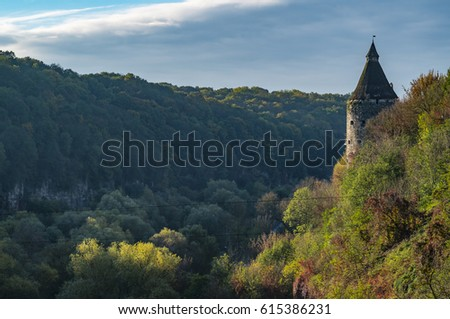 A watchtower above the canyon of the Smotrych River in Kamianets-Podilskyi, Western Ukraine. Trees are showing their autumn colours.