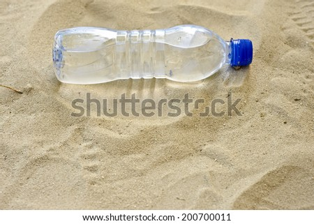a water bottle in the sand - stock photo