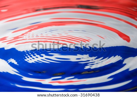 A water droplet against a Dutch / Netherland flag colors